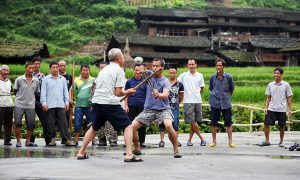 "Pic shows: Some people practicing Kung Fu.  Locals in this village have every reason to be proud of their martial arts skills, after all not only have they been practising for three centuries – they even have a martial arts discipline named after them.  And far from being a dying art, it's now so popular in Gundi village in Tianzhu County, in south-west China's Guizhou Province, that even the women and the children join in as well as the men.  Despite its official name the village is better known as ""kung fu village"", as all of its residents have a habit of regularly practicing martial arts in the mornings and evenings.  The 123 households comprise Dong people, one of China's many ethnic minorities, who have been living in the region for hundreds of years.  The Dong even developed their own fighting technique known as the Black Tiger style, or ""Heihuquan"" in Chinese, which is characterised by its extensive footwork, acrobatic kicks, low, wide stance, and unique fist positioning.  The fighting style also has a history of 300 years and has been kept alive with the regular practice sessions.  As for the reason behind the popularity of kung fu in the village, locals claimed its roots lie in their ancestors' need to defend themselves and their livestock from predators and bandits descending from the surrounding mountains.  Others said it was because the Dong people were often discriminated against in the past and felt the need to stand up for themselves.  In the past, only men practiced martial arts, but now women have also joined in. The tradition is also handed down from generation to generation.  The villagers say they now practice the Black Tiger style for health reasons, although they also point out that it could still be useful if they ever have to fight off any ill-intentioned visitors.  (ends)"
